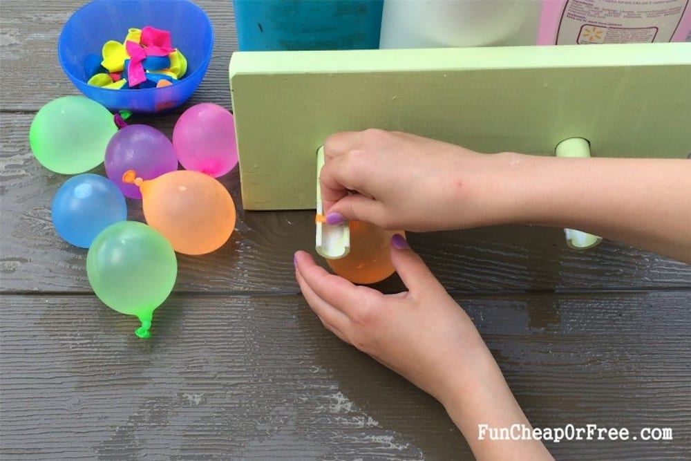girl using water balloon filler station to tie balloons, from Fun Cheap or Free