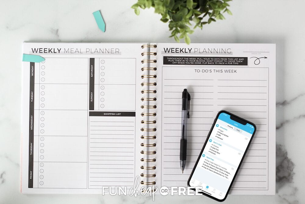 Open planner with a smartphone with a planning app on top from Fun Cheap or Free