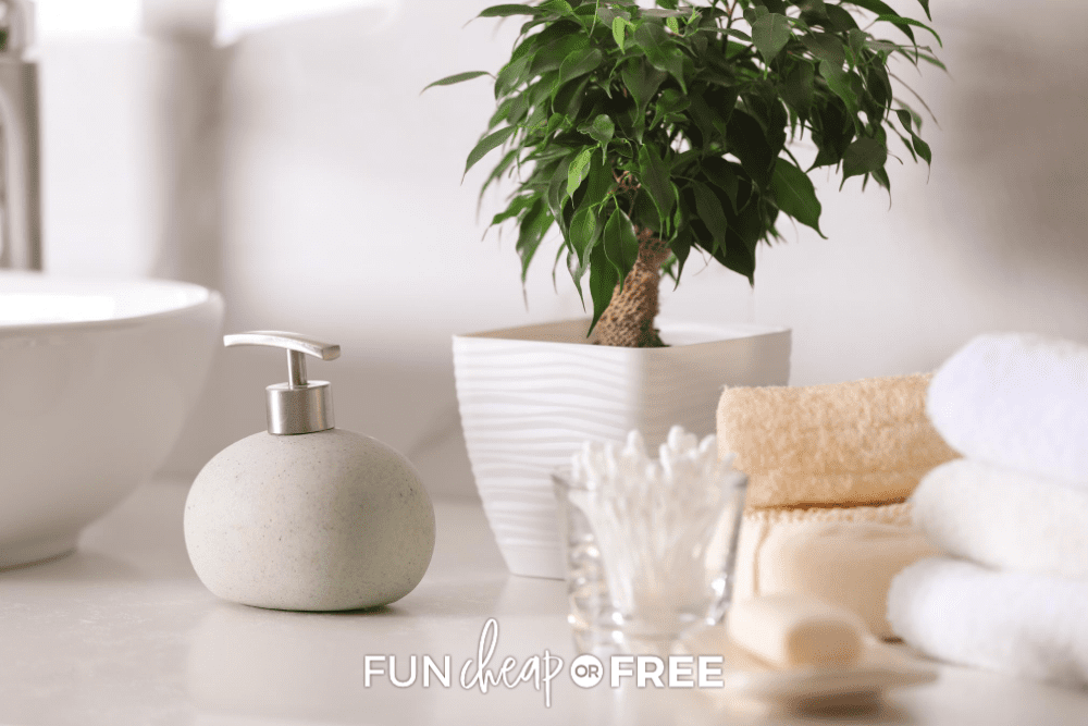 bathroom counter with soap dispenser, cotton swabs and towels from Fun Cheap or Free