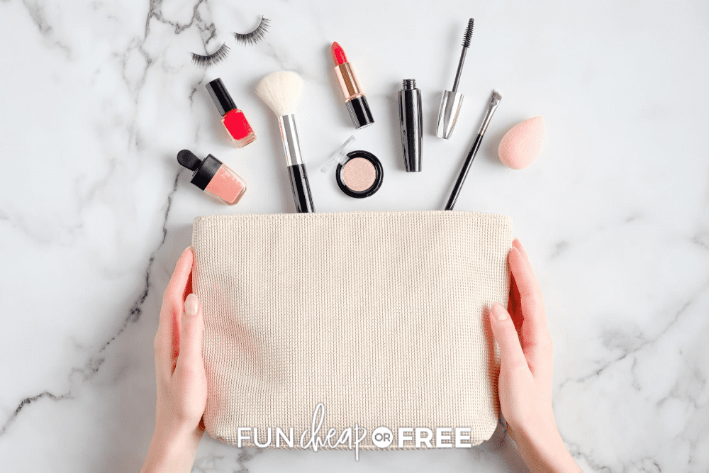 makeup bag held in womans hands spilled on a marble countertop from FunCheaporFree