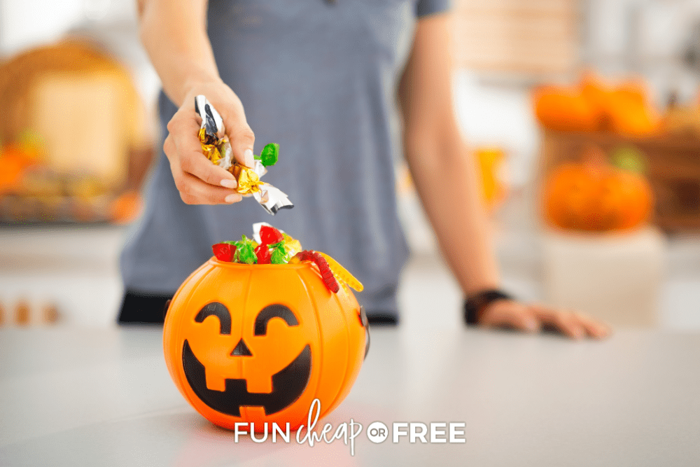woman grabbing leftover Halloween candy from a pumpkin bucket, from Fun Cheap or Free