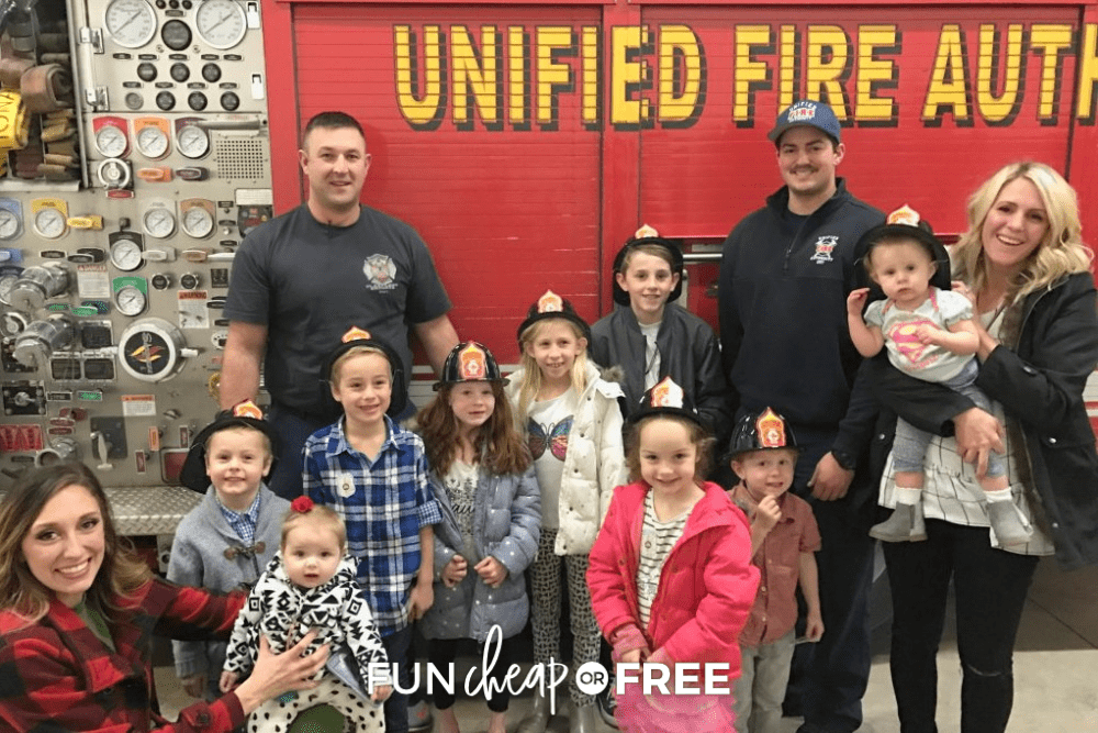 People standing with firefighters at a fire station, from Fun Cheap or Free