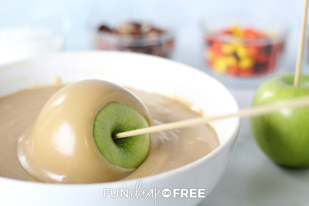 Apple on a skewer being dipped in caramel, from Fun Cheap or Free