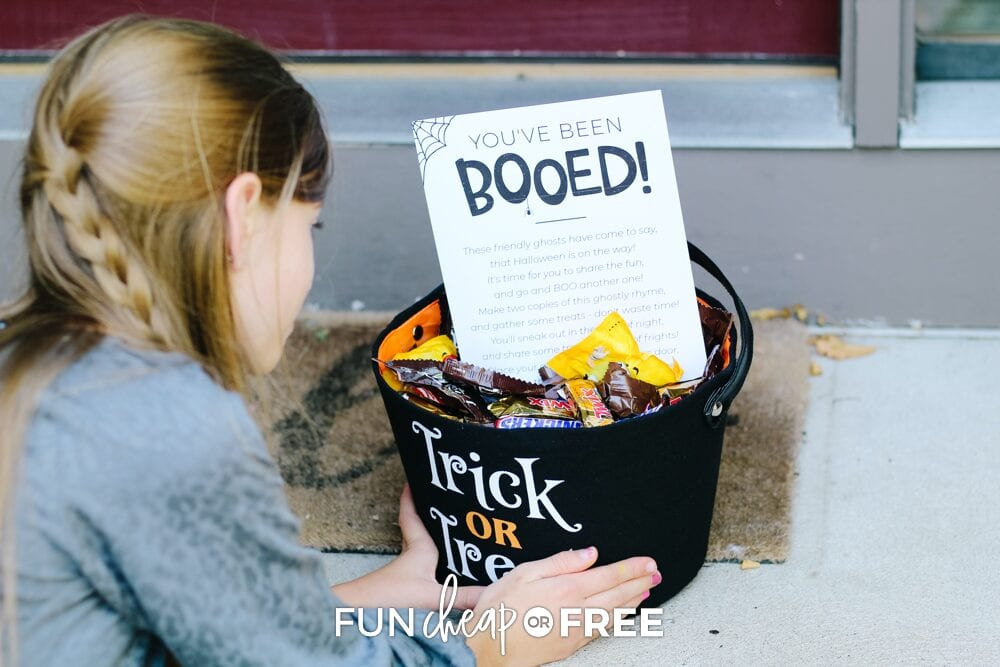 Girl putting You've been booed printable and gift on porch, from Fun Cheap or Free