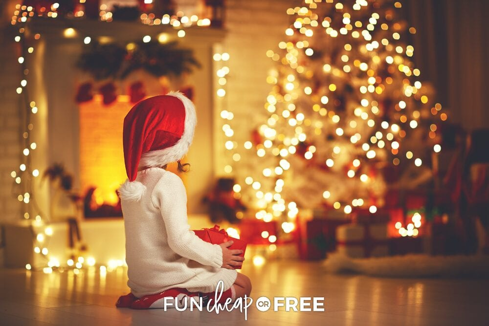 Little girl holding present sitting in front of Christmas tree, from Fun Cheap or Free
