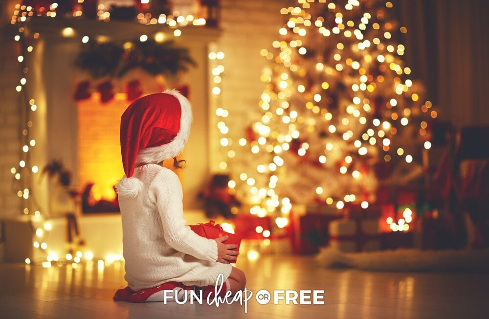Little girl holding present in front of tree, from Fun Cheap or Free