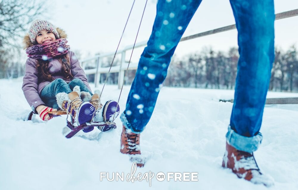 Father pulling daughter in snowy sled, from Fun Cheap or Free