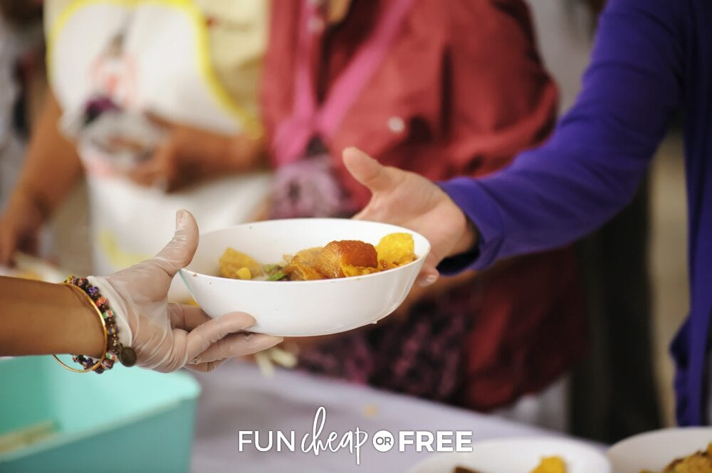 Volunteer handing food out, from Fun Cheap or Free