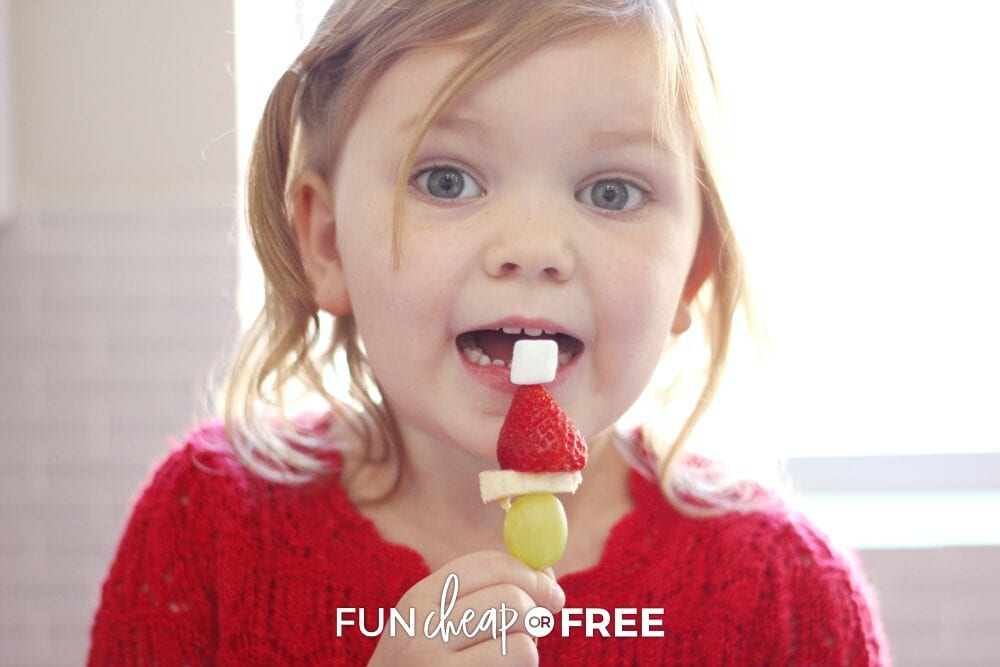 Girl eating Grinch skewers, from Fun Cheap or Free