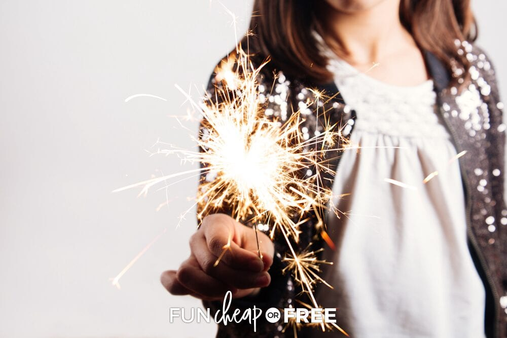 Little girl holding sparkler for New Year's Eve traditions, from Fun Cheap or Free