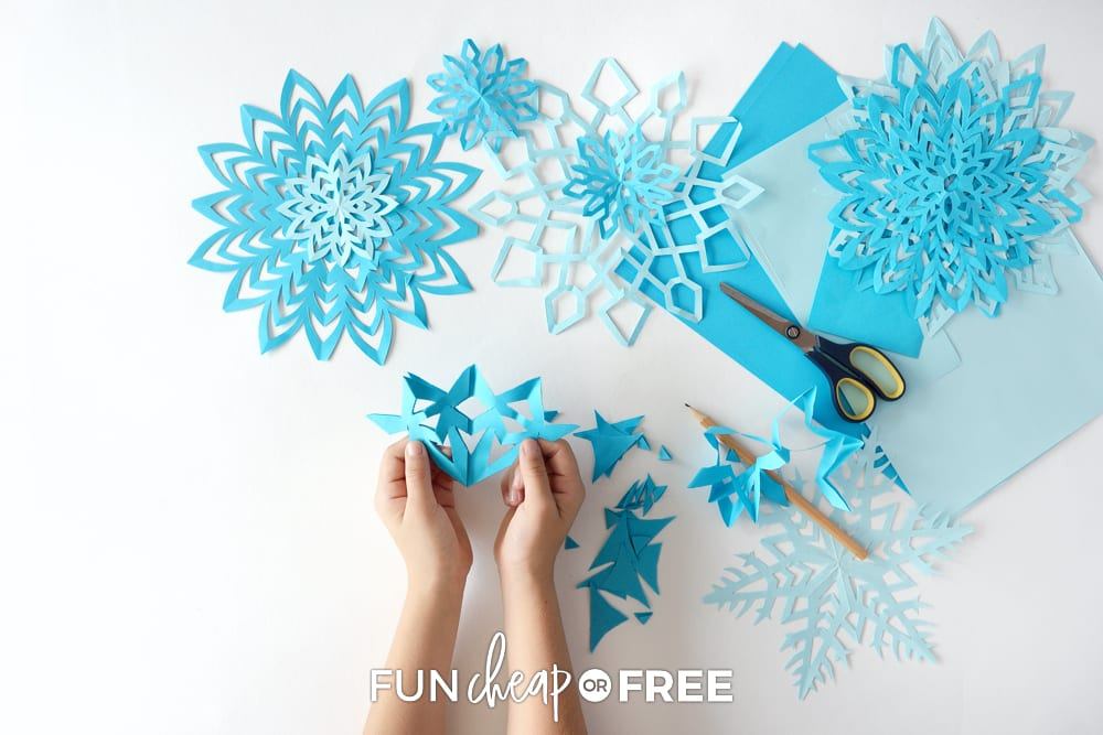Hands making paper snowflakes, from Fun Cheap or Free