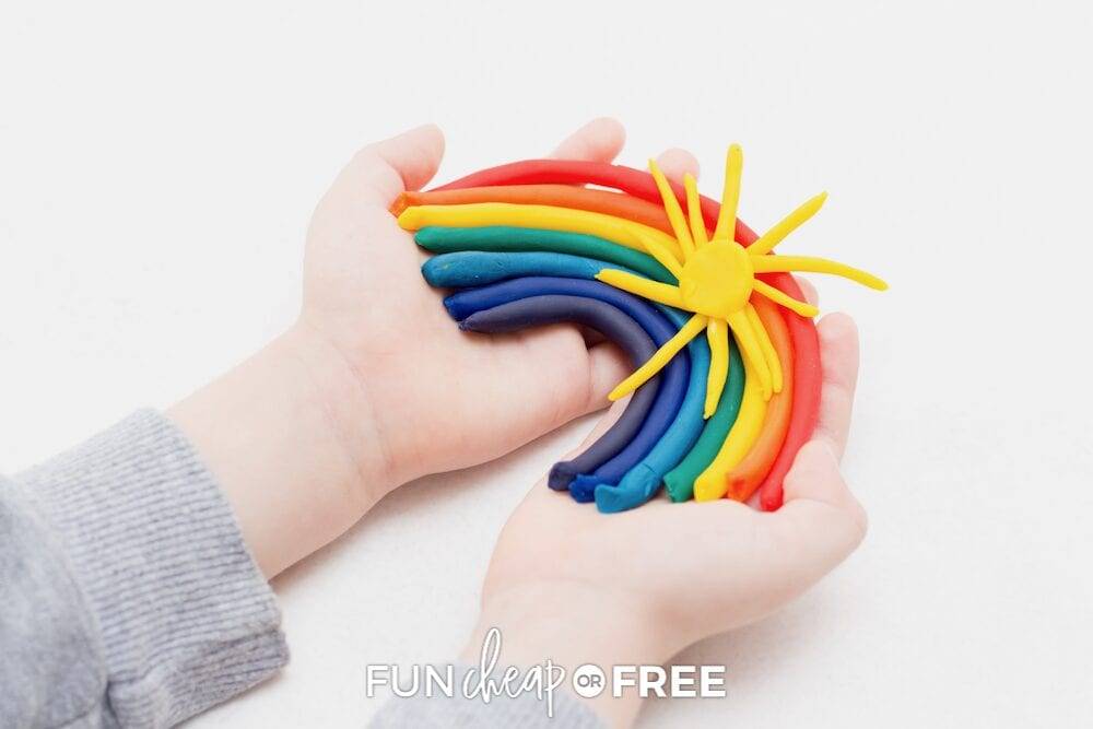 Child holding a playdough rainbow, from Fun Cheap or Free