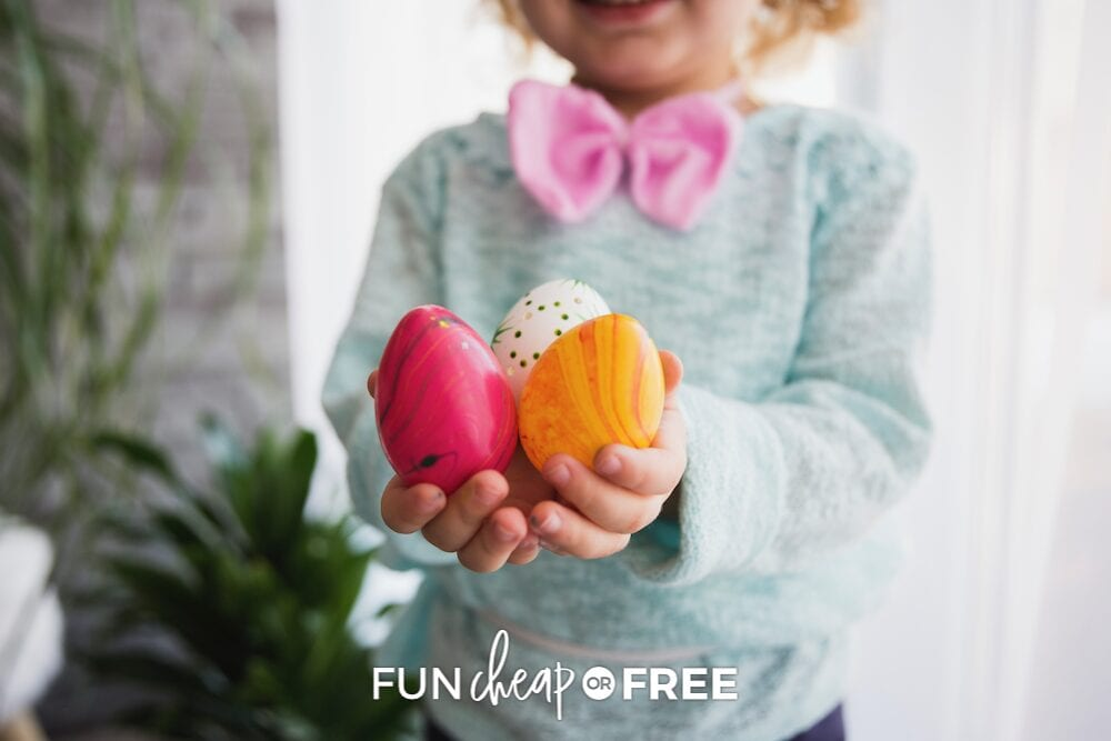 little kid holding plastic Easter eggs, from Fun Cheap or Free