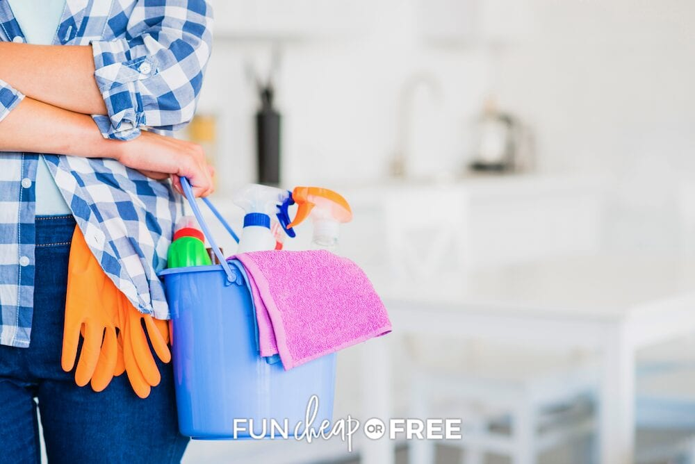 Woman holding cleaning supplies to stay on her cleaning schedule from Fun Cheap or Free