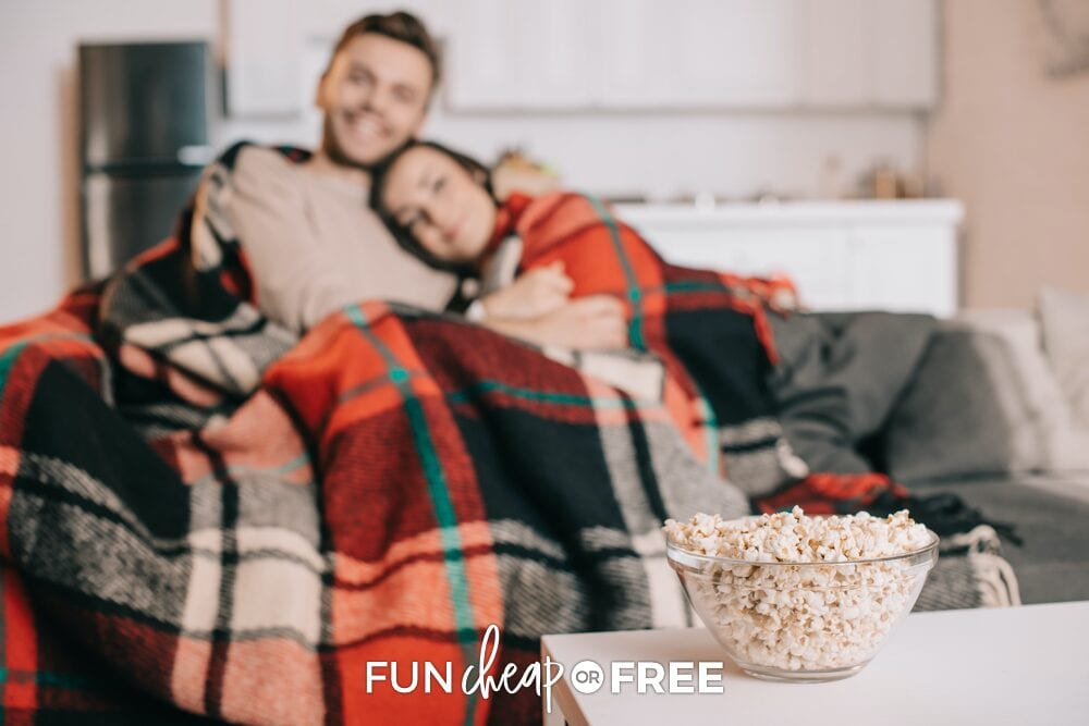Couple snuggling on a couch with popcorn representing ways to save money at home, from Fun Cheap or Free