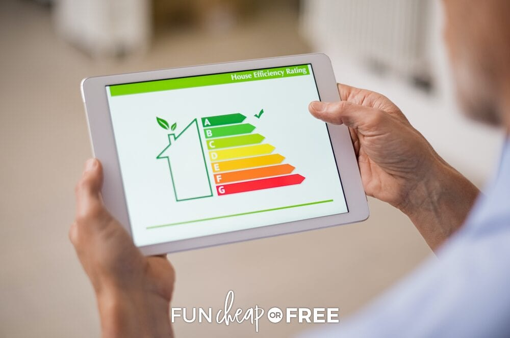 Man holding a tablet looking at house efficiency rating as ways to save money, from Fun Cheap or Free