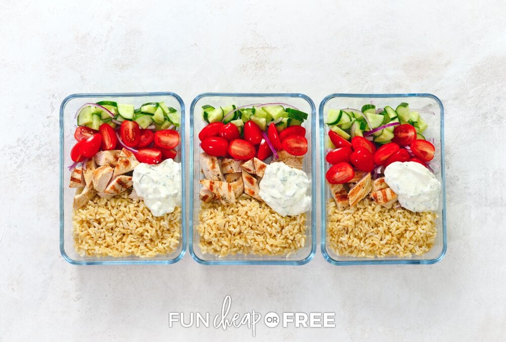 Meal prep containers with rice, chicken, tomatoes, cucumbers, and dip on a countertop, from Fun Cheap or Free