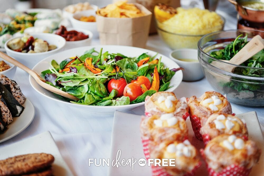 Bowl of salad, cupcakes, chips, and various foods laid out on a serving table, from Fun Cheap or Free