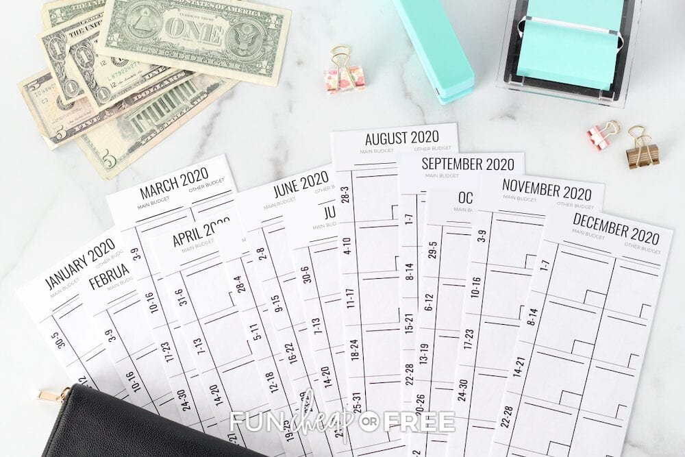 Envelope budget system fanned out on a counter with dollar bills and office supplies, from Fun Cheap or Free