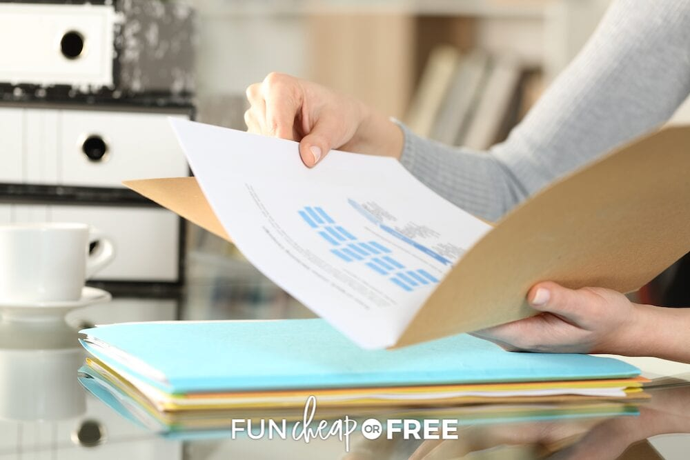 A woman holding an open file folder while she sorts clutter, from Fun Cheap or Free!