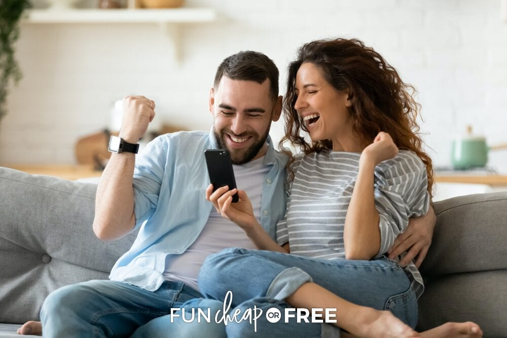 A man and a woman on a couch celebrating while looking at a cell phone, from Fun Cheap or Free
