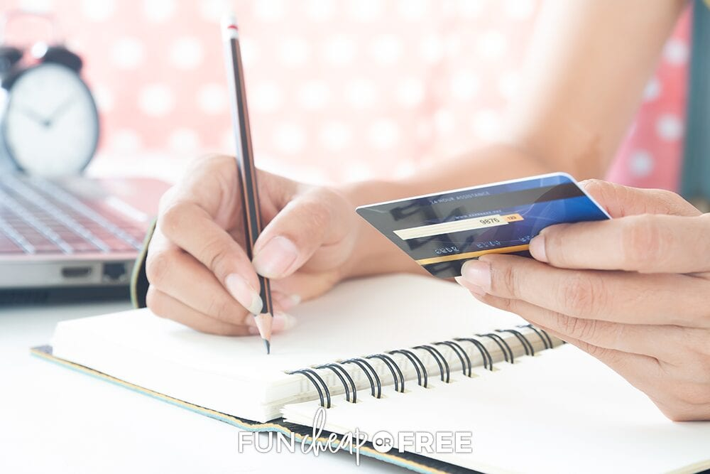 A woman holding a credit card and writing to track credit card debt, from Fun Cheap or Free