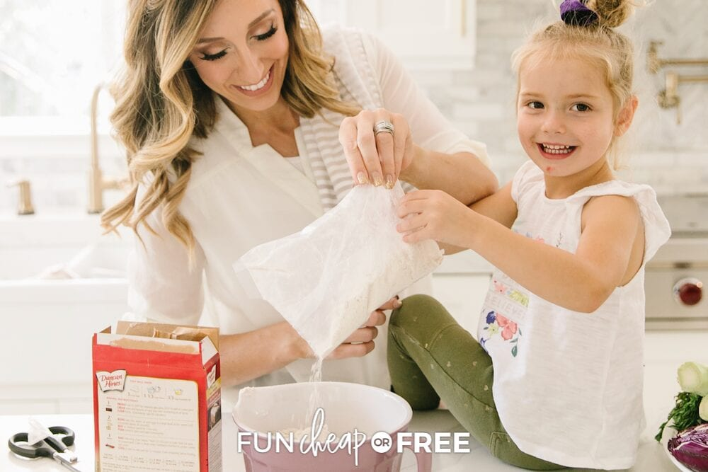 Jordan in the kitchen with her daughter, pouring cake mix into a bowl, from Fun Cheap or Free.