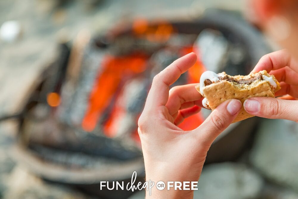 Hands holding a s'more next to a fire pit, from Fun Cheap or Free