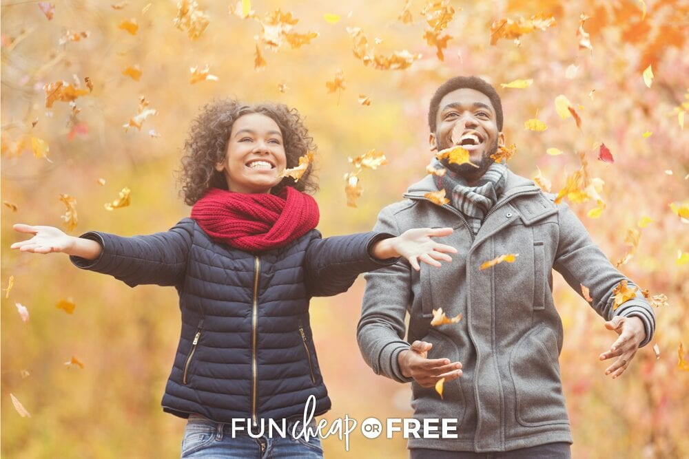 A young couple laughing and playing with leaves on a fall date, from Fun Cheap or Free