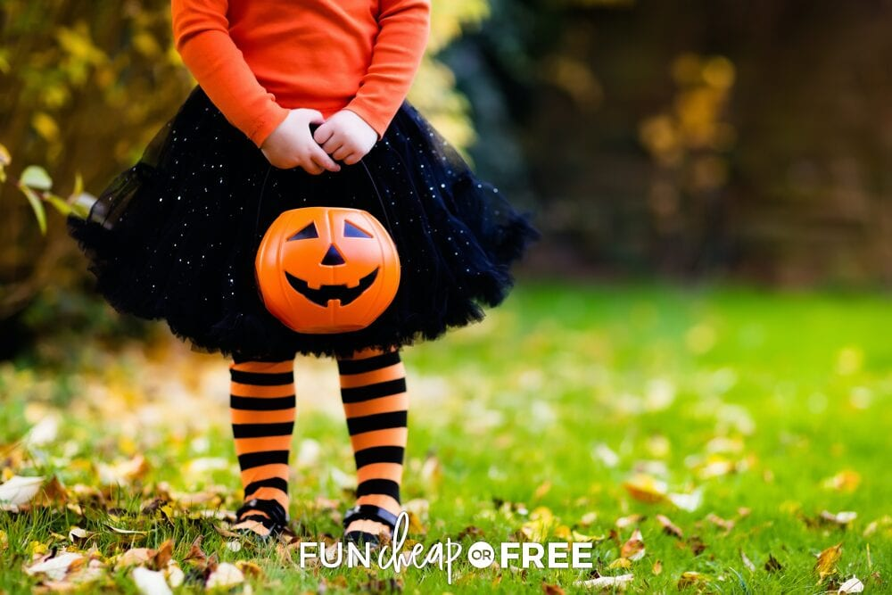 Little girl holding trick or treat bucket ready for Halloween as part of fall bucket list, from Fun Cheap or Free
