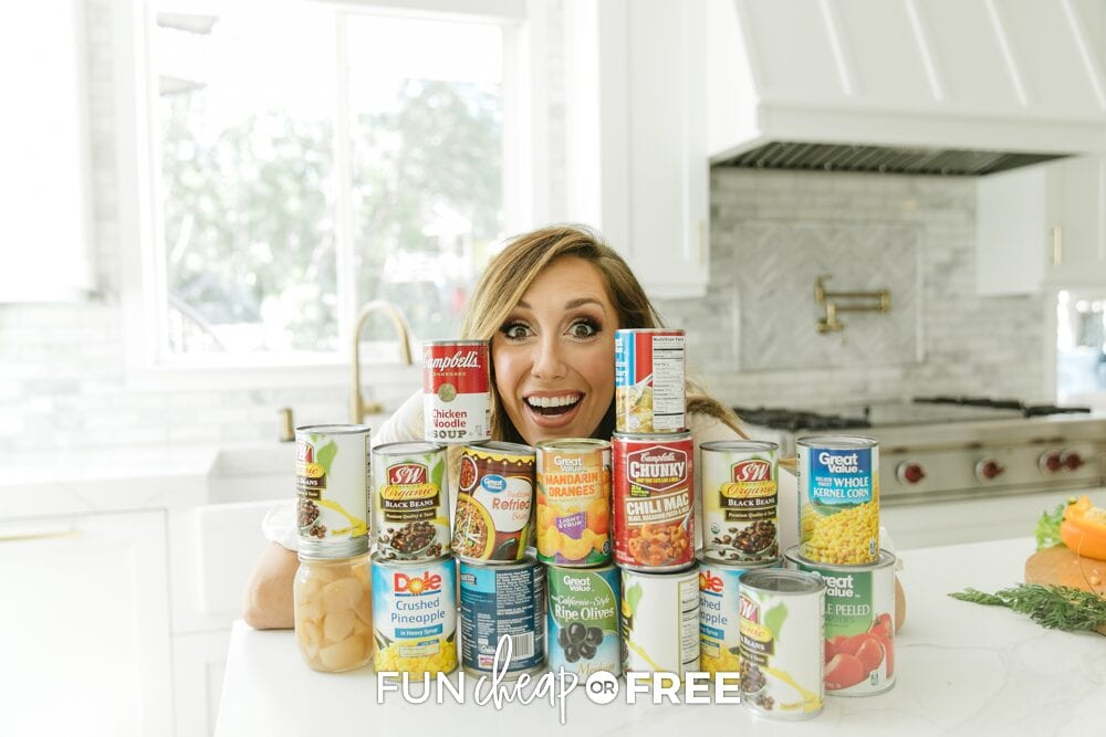 Jordan smiling with canned goods stacked on the counter, representing Shelftember, from Fun Cheap or Free