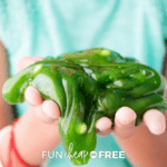 woman wearing green shirt holding green slime