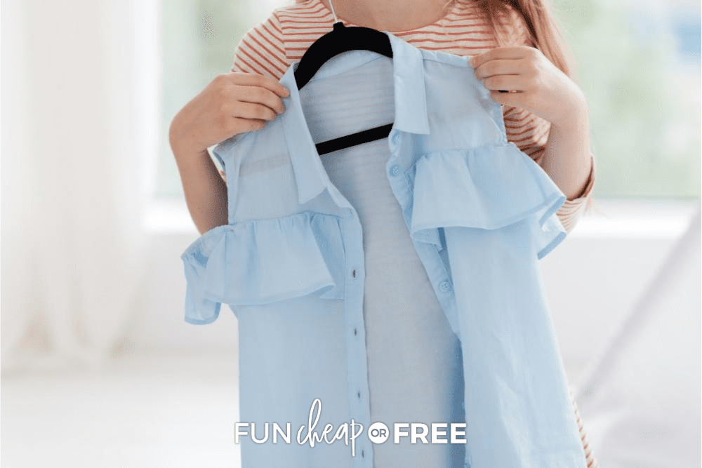 Young woman holding up a blue blouse from Fun Cheap or Free