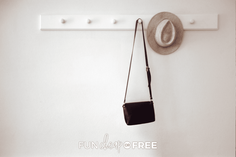 Wall pegs with a purse and a hat for closet organization, from Fun Cheap or Free