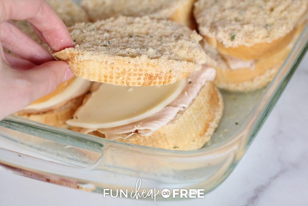 Hand assembling baked Italian sandwich recipe, from Fun Cheap or Free
