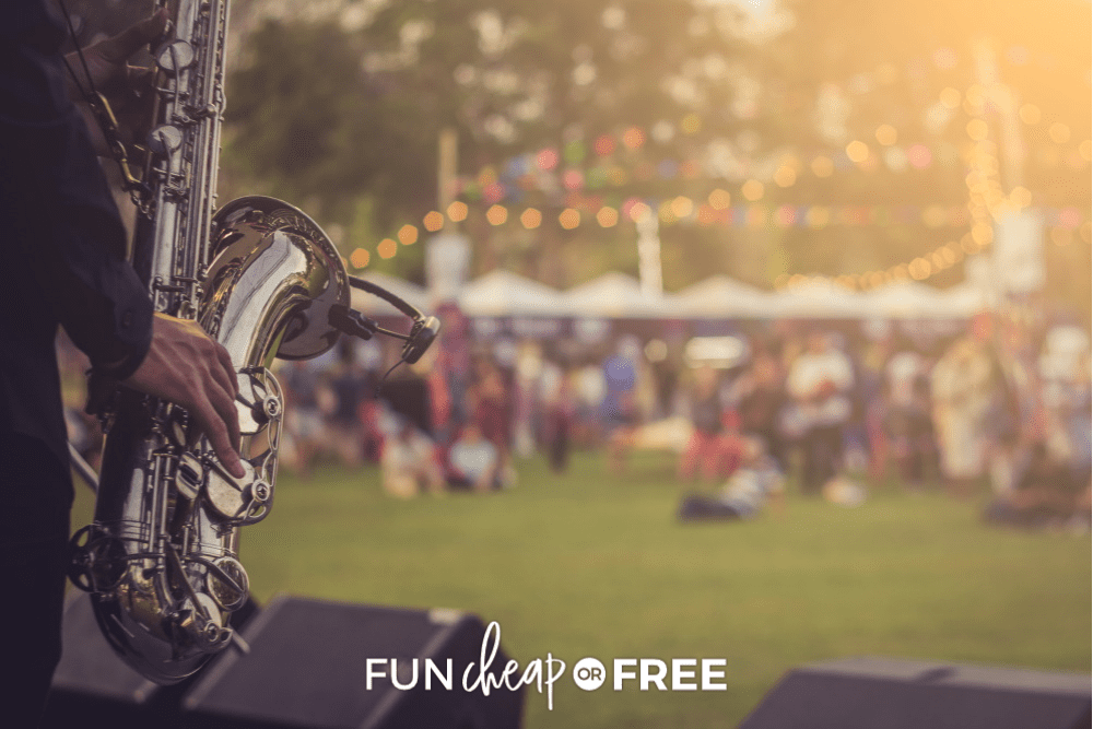 Person playing a saxophone for an audience at an outdoor concert, from fun cheap or free