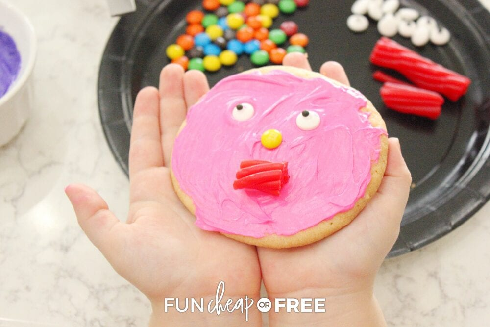 Girl holding decorated monster cookie as part of Halloween party themes, from Fun Cheap or Free