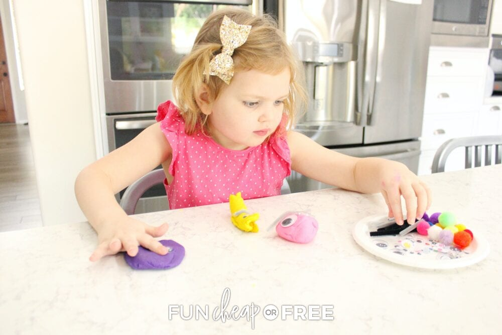 Girl playing with playdough making a monster on a counter, from Fun Cheap or Free