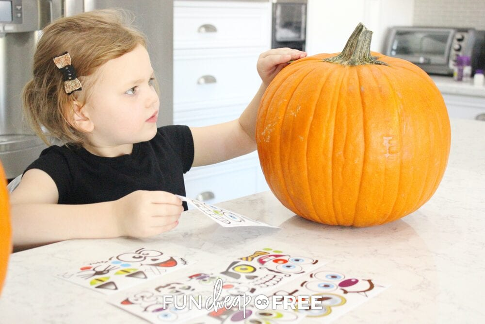 Little girl decorating pumpkin with stickers on a counter, from Fun Cheap or Free