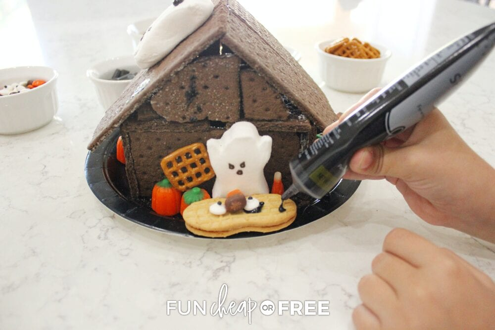 Hand decorating haunted cookie house for fun Halloween party themes, from Fun Cheap or Free