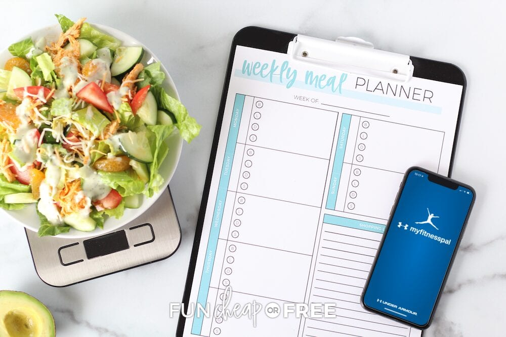 Weekly meal planner on a clipboard with MyFitnessPal app open on a smartphone, from Fun Cheap or Free