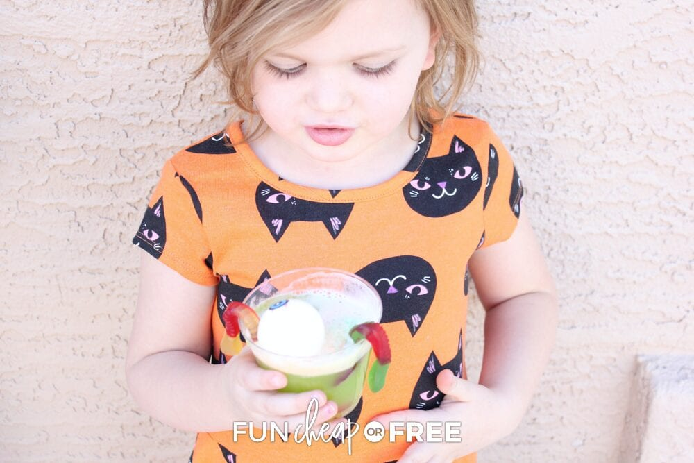 Girl holding witch's brew drink with gummy worms, from Fun Cheap or Free