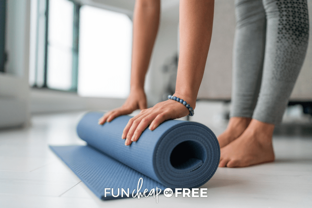 woman wearing gray yoga pants bends over to roll up blue yoga mat, from Fun Cheap or Free