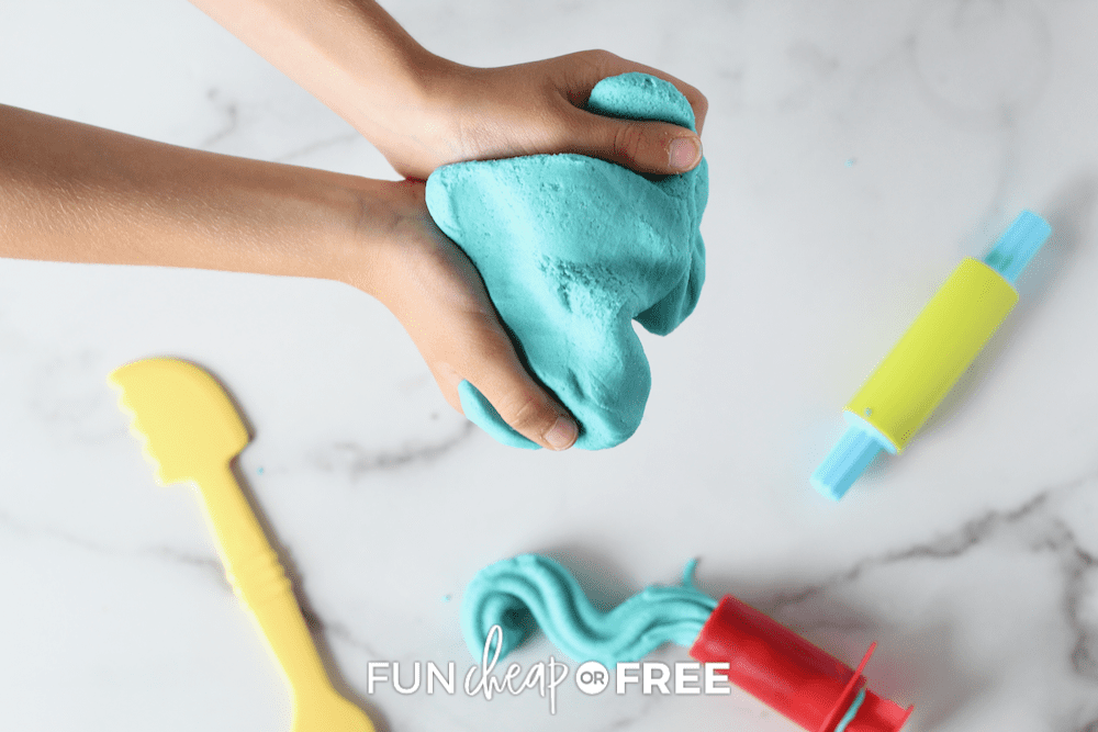 woman's hands holding blue playdough, from Fun Cheap or Free