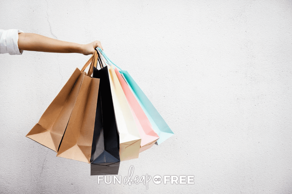 woman standing in front of a white background holds six shopping bags, from Fun Cheap or Free