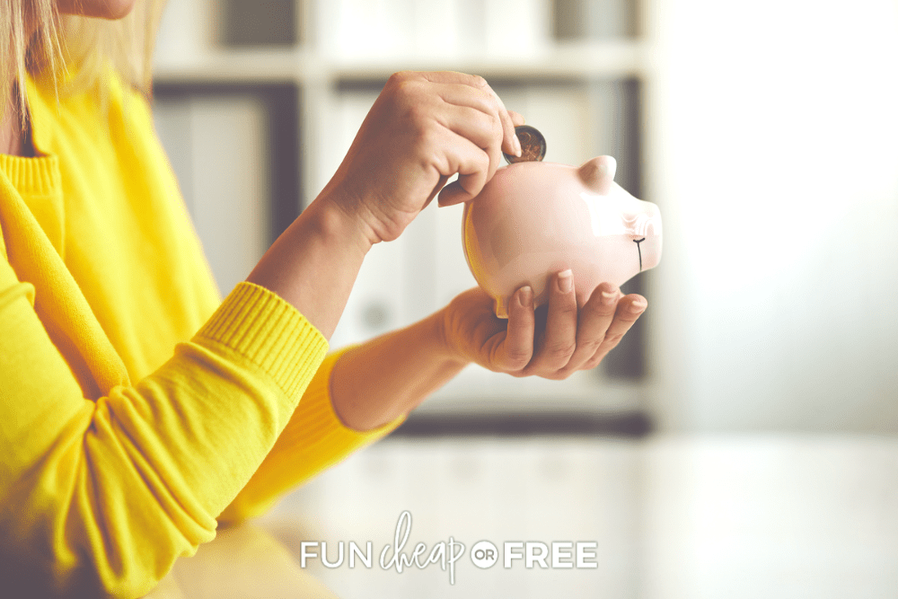 Woman wearing a yellow sweater puts a quarter into the piggy bank she's holding, from Fun Cheap or Free