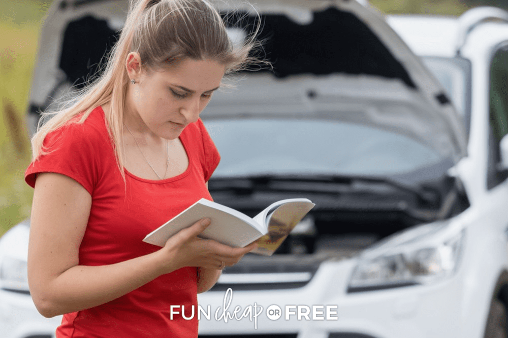 woman with red t shirt reading her auto manual in front of her car from Fun Cheap or Free