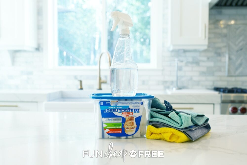 Spray bottle, magic erasers, and microfiber cloths on a counter, from Fun Cheap or Free