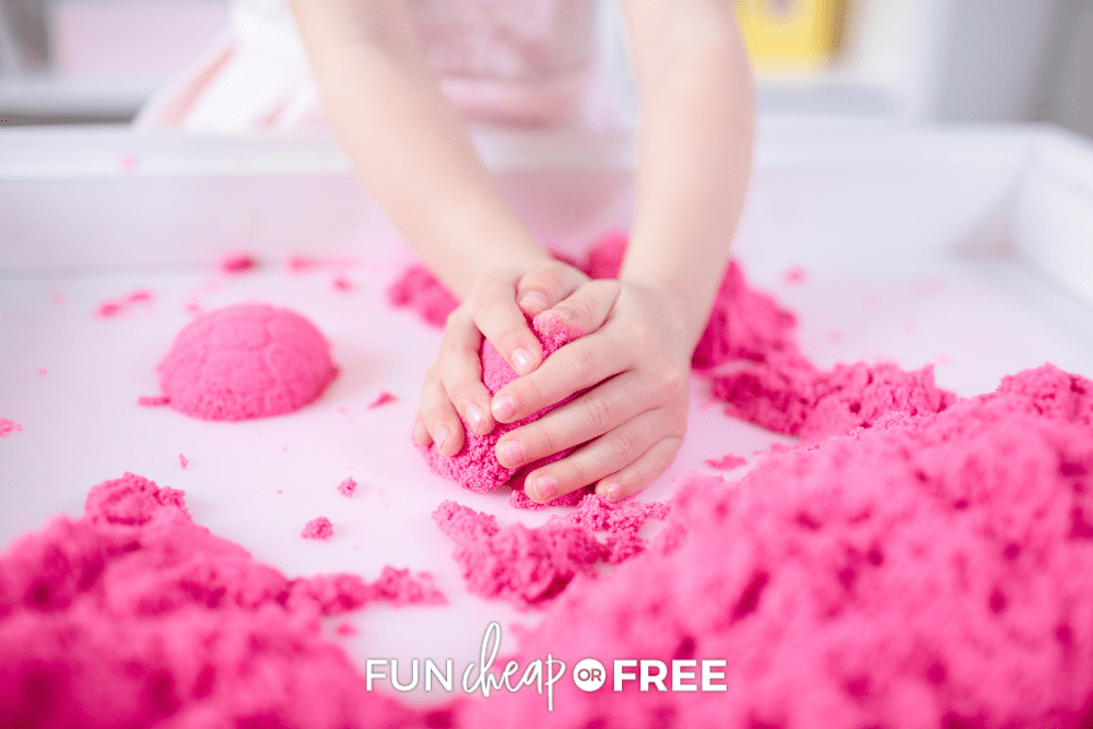 hands playing with pink kinetic sand, from Fun Cheap or Free