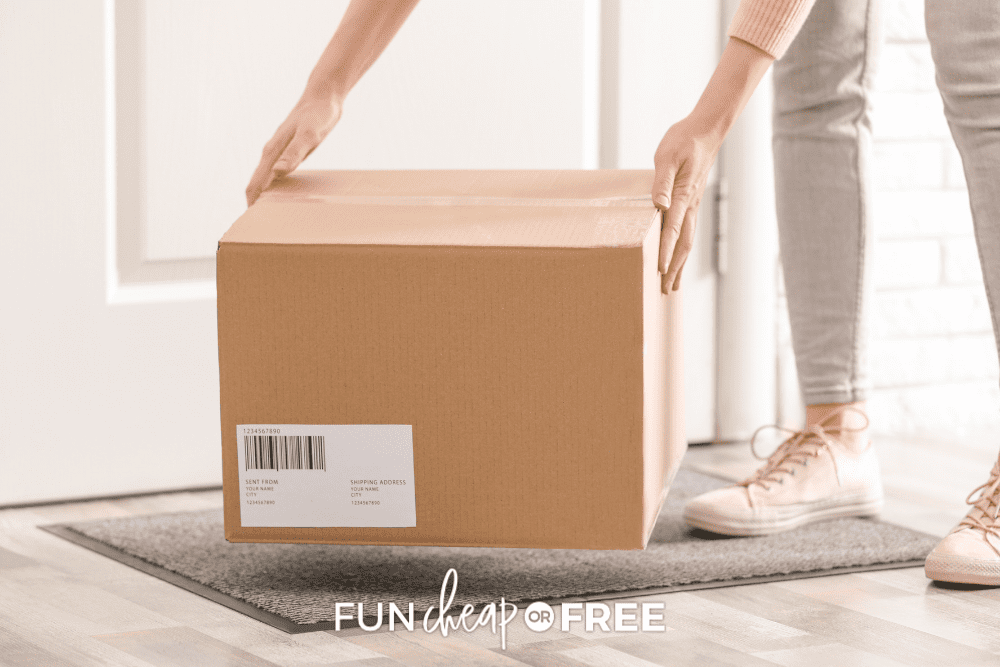 Woman in pink top and grey jeans picking up package from front door step, from Fun Cheap or Free